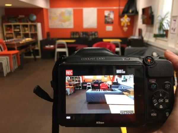 Foto vom Display einer Kamera, die gerade eine Video-Aufnahme von einem Raum macht, in dem zwei Couchen, zwei Tische und mehrerer Stühle zu sehen sind.