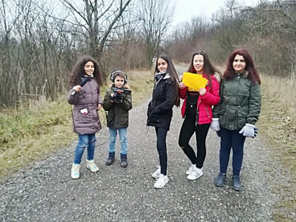 Vier Mädchen und ein etwas jüngerer Bursche stehen auf auf einem Schotterweg in einem lichten Wald. Das Mädchen ganz links hält ein Mikrofon, der Bursche neben ihr eine Videokamera. Ein weiters Mädchen hält mehrerer Zettel, auf denen was geschrieben steht.