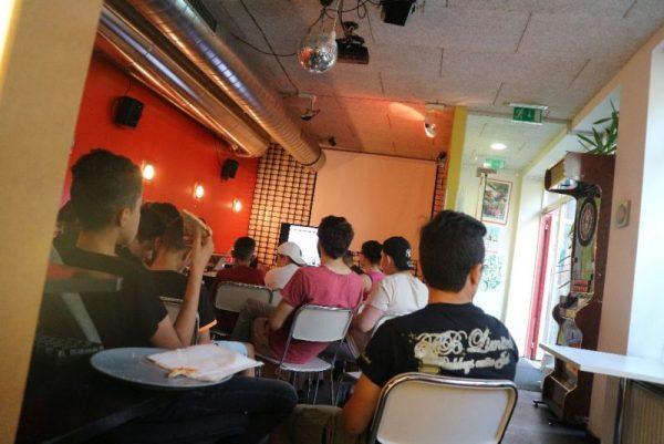 Eine Gruppe von jungen Burschen sitzt in einem Jugendlokal. Alle sind von Hinten zu sehen und schauen nach vorne wo ein Fernseher steht.