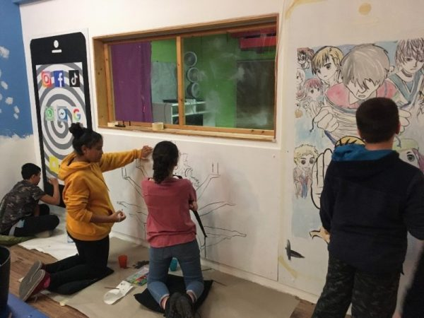Vier Jugendliche malen an verschiedenen Bildern, die menschengroße Handydisplays darstellen, sowie an einer indischen Göttinnenfigur, mit mehreren Armen, die alle Handys in der Hand halten.