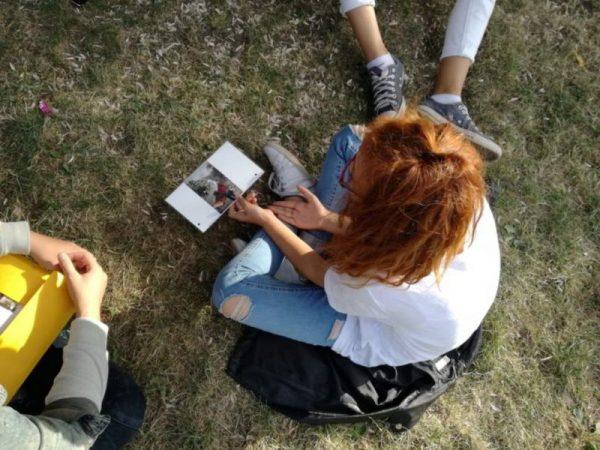 Ausder Vogelperspektive fotografiert; Ein Mädchen sitzt im Schneidersitz im Grad und betrachtet ein Foto, das sie in ihrer Hand hält, daneben sieht man die Füße eines anderen und die Hände eines weiteren Kindes.
