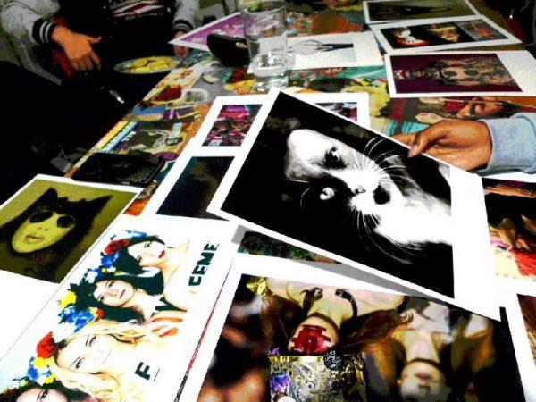 Ausdrucke von verschiedenen Fotos liegen auf einem Tisch, eine Hand hält eine Foto, auf dem ein Gesicht zu sehen ist, welches als Katze verfremdet wurde.