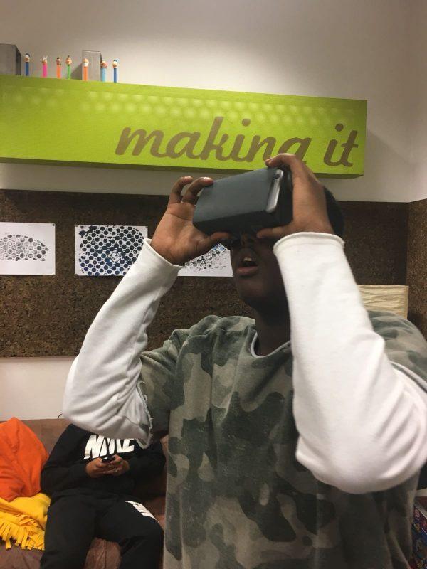 Ein Bursche hält sich eine VR-Brille vor die Augen und hat staunend den Mund geöffnet.
