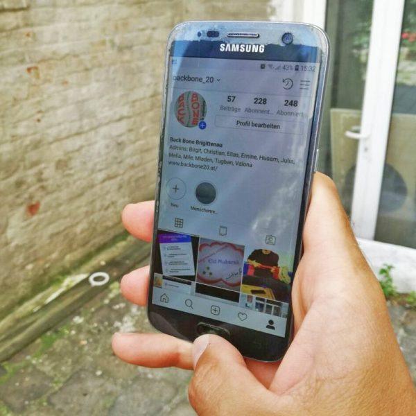 Eine Hand streckt ein Handy ins Bild, am Bildschirm sind Informationen zum Verein backbone zu lesen.