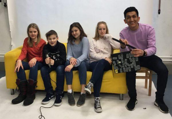 Drei Mädchen und zwei Burschen sitzen auf einem gelben Sofa, bzw auf einem Hocker daneben. Ein Bursche hält ein Mikro in der Hand, der andere eine Filmklappe.