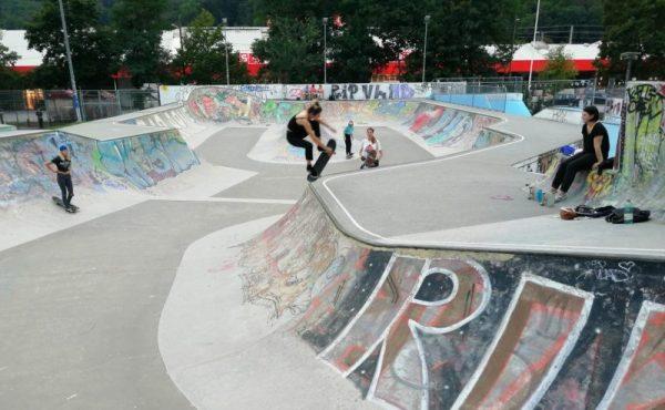 In einem Skatepark skaten ein paar Mädchen mit ihren Board, eine Frau sitzt am Rand und sieht zu.