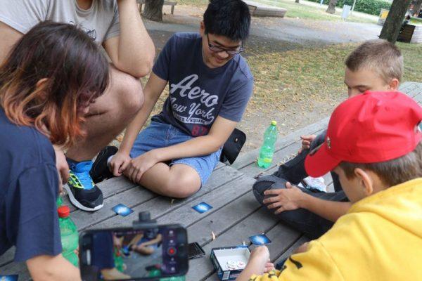 Vier Kinder und ein Jugendarbeit sitzen im Freien auf einer Holzpritsche und speilen ein Spiel mit Kärtchen und Blättchen.