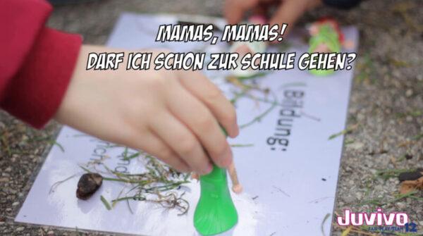 Eine verschwoḿmene Hand hält etwas kleines Grünes über ein Blatt Papier, auf dem einzelne Buchstaben zu lesen sind und auf dem vereinzelt Grashalme liegen.