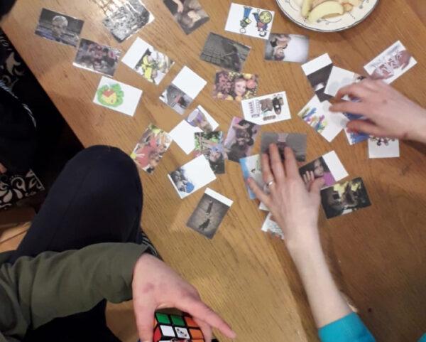 Menschenrechte-Memory, ca. 20 Bildkarten liegen auf einem Tisch, zwei Hände sortieren die Bilder.