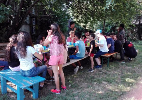 Ca 15 Kinder sitzen auf Holzbänken rund um mehrere Tische und essen und trinken und unterhalten sich.