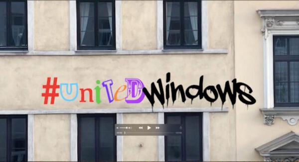 Foto einer eher dreckigen und gelben Häuserwand mit vielen Fenstern. Darüber steht in bunten Lettern geschrieben: #UnitedWindows.
