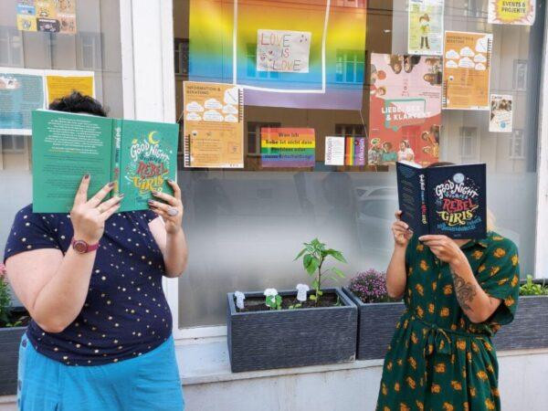 """Zwei Frauen in bunten Klamotten stehen vor einem Auslagenfenster. Sie stehen und lesen intensiv das Buch """"Good Night Stories for Rebel Girls: 100 außergewöhnliche Frauen."""""""