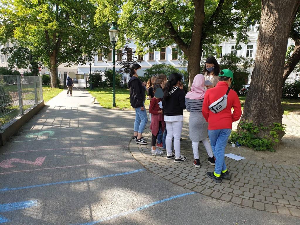 Zu sehen ist eine Szene in einem Wiener Park bei Sonnenschein. Rechts bei einem Baum ist eine Gruppe von Kindern versammelt, die aufmerksam einer Betreuerin, die einen Mund-Nasen-Schutz auf hat, zuhören. Im Hintergrund geht eine Person mit einem kleinen weißen Hund. Im Vordergrund sind mit Straßenmalkreiden Zahlen und Felder auf den Asphalt gemalt.