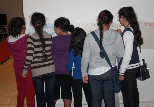 Eine Gruppe von Mädchen ist von hinten zu sehen, wie sie etwas auf Plakate an der Wand eintragen