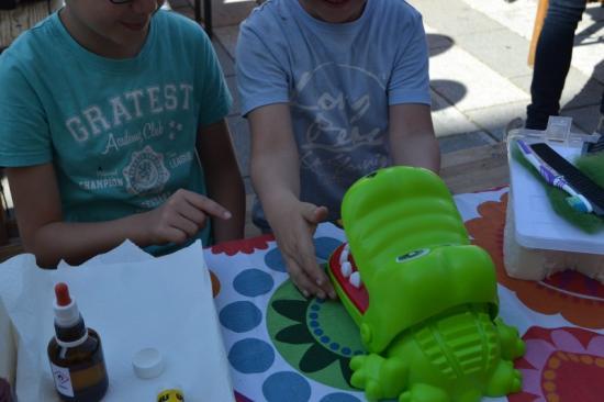 Zwei Kinder im Park beschäftigen sich spielerisch mit der Mundgesundheit von einem grünen Spielzeugkrokodil