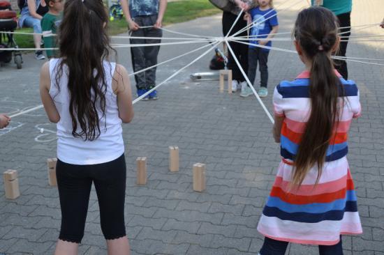 """Kinder stehen im Park im Kreis und halten mit Schnüren den sogenannten """"Fröbelturm"""" in die Höhe."""