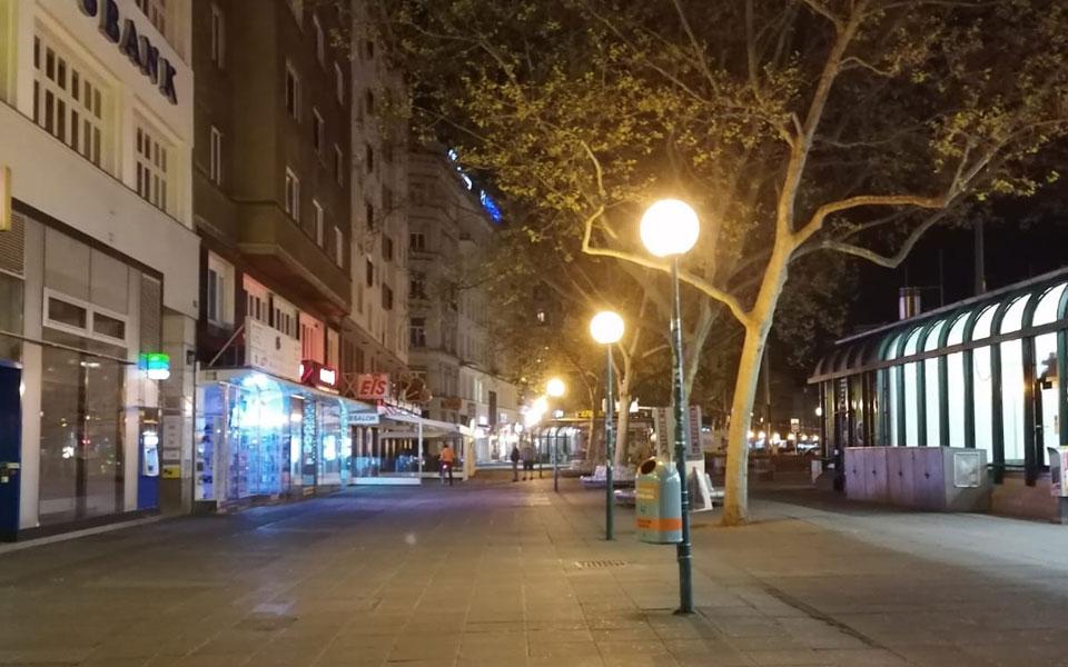 Eine menschenleere Straße bei Dunkelheit, in der Mitte ist eine Reihe von Straßenlaternen. Am linken Bildrand sind Auslagen von Geschäftslokale zu sehen. Am rechten Bildrand ist eine U-Bahn-Station zu erkennen.