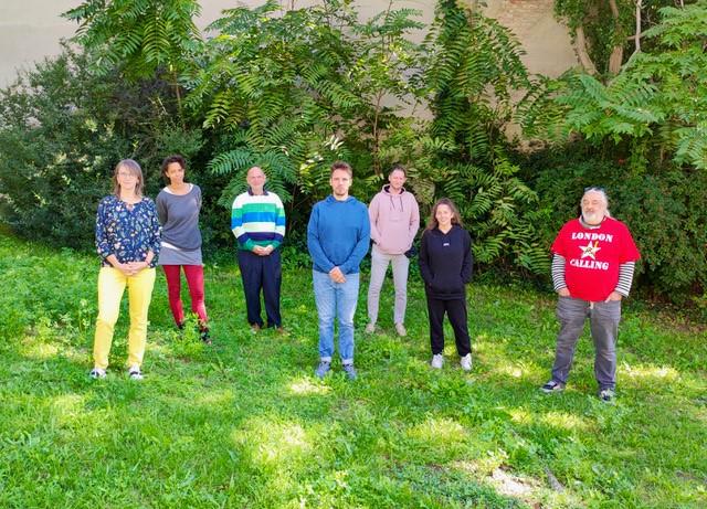 Die sieben Mitglieder der aktuellen Blogredaktion stehen in einer Wiese vor einer grün bewachsenen Wand.